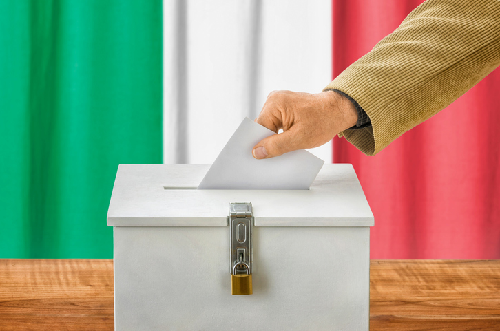 Man putting a ballot into a voting box - Italy